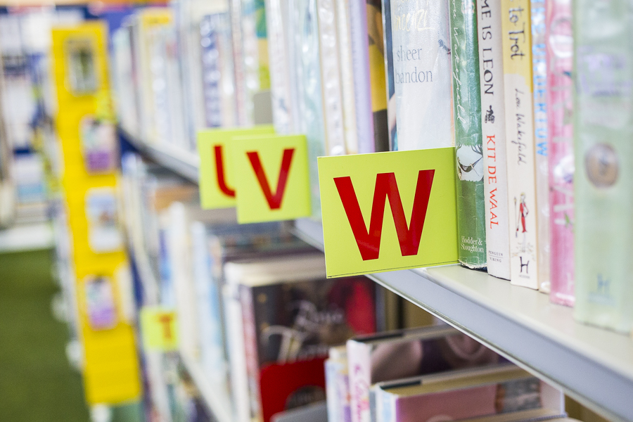 Shelves of books in Minchinhampton Community Library showing the letter W