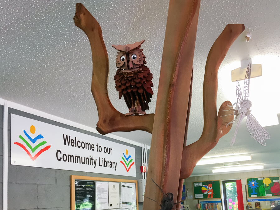 Wooden owl at desk with Welcome sign behind